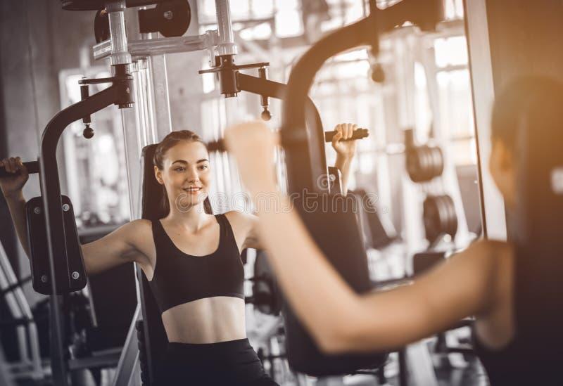 Dysponowany piękny młodej kobiety ćwiczenia trening na maszynie w gym Uradowana uśmiechnięta dziewczyna jest cieszy się z jej sta zdjęcie royalty free