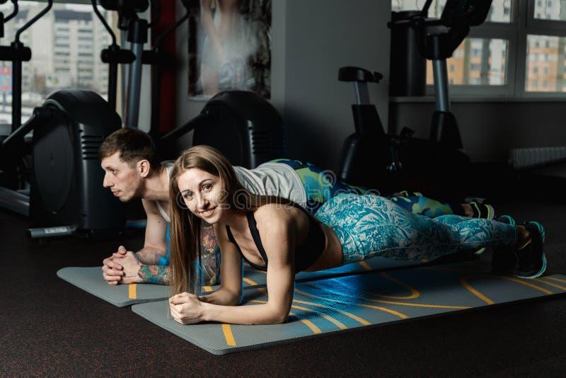 Dysponowany sportive mężczyzna i kobieta robi deski sedna ćwiczenia szkoleniu popieramy mięśnia pojęcia gym sporta sportowa spraw zdjęcie royalty free