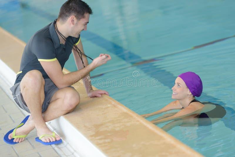 Dysponowany trener opowiada pływaczka w czasu wolnego centrum fotografia royalty free