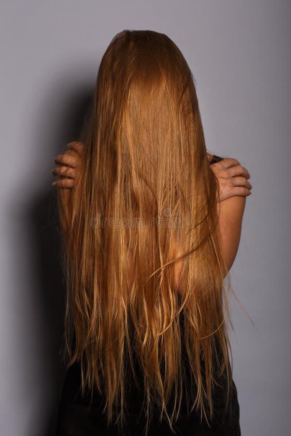 Dyster deprimerad kvinna i svartkläder med långt blont hår Co arkivbilder