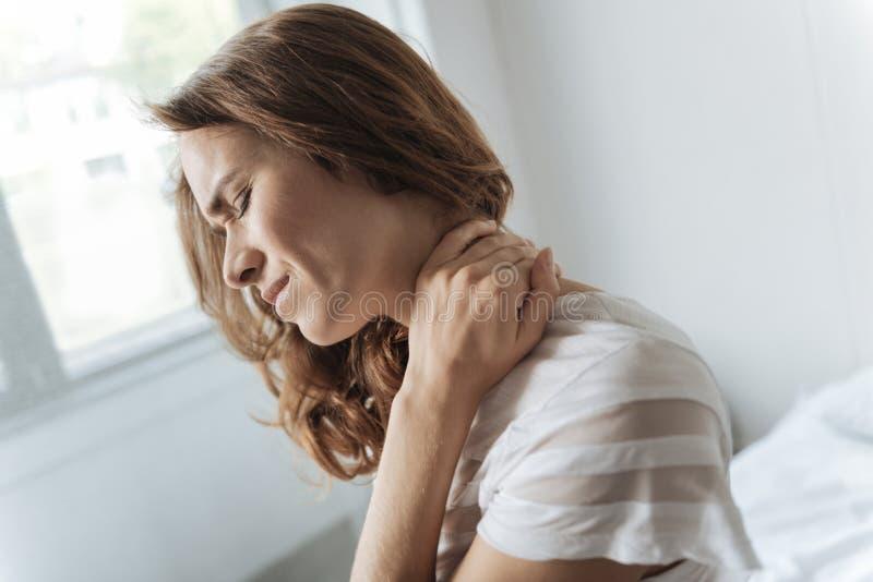 Dyster dyster kvinna som trycker på hennes hals royaltyfri fotografi