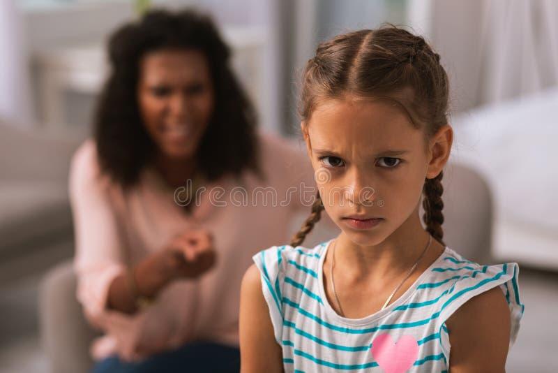 Dyster gullig flicka som hemma ser dig arkivfoton