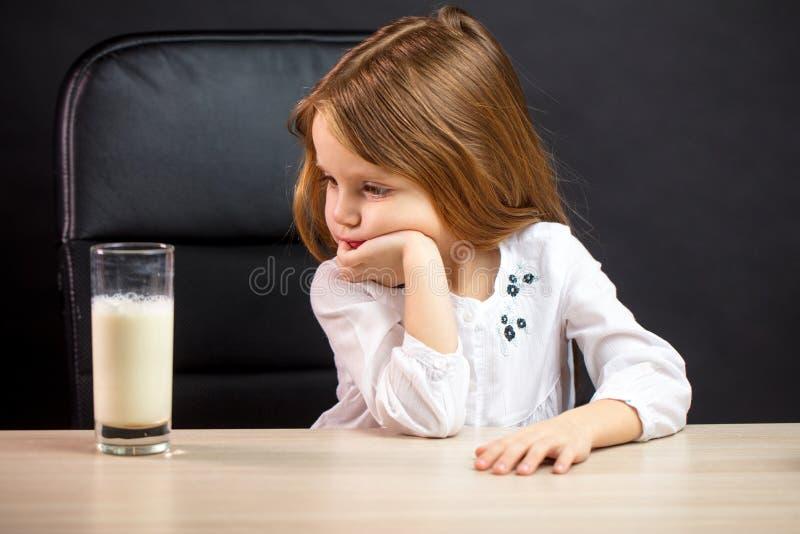 Dyster liten flicka i exponeringsglas som vägrar att dricka för att mjölka, över svart royaltyfria bilder