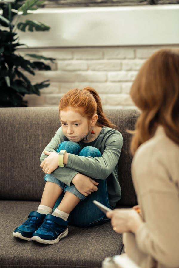 Dyster olycklig flicka som sätter hakan på hennes knä royaltyfri foto