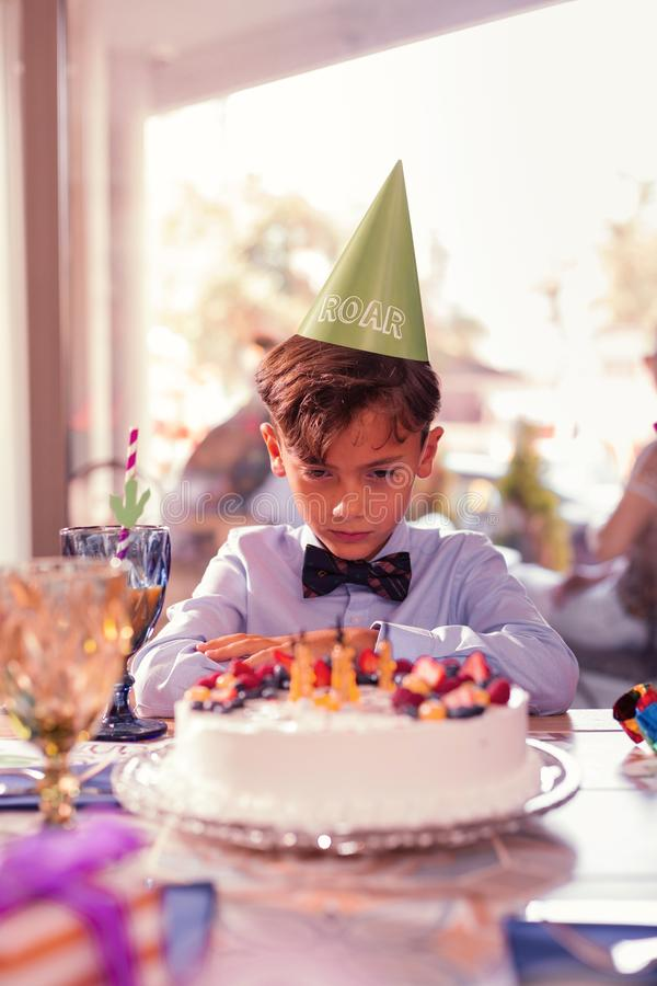 Dyster pojkekänsla som är ledsen och ser födelsedagkakan arkivbild