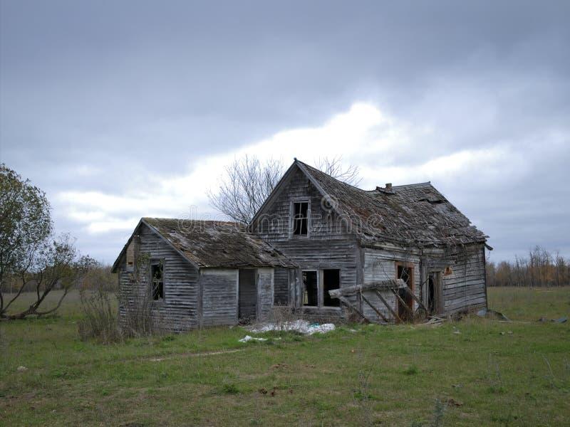Dystert övergett förfallet lantgårdhus med molniga himlar royaltyfri foto
