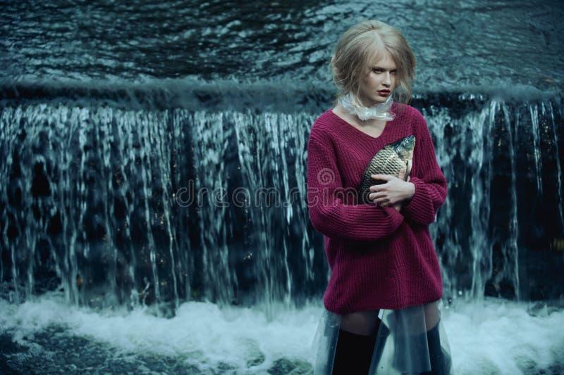 Dystopian modestående av modellen med den döda fisken i floden av kloak mot vattenfallet av smutsigt och förorenat vatten royaltyfria bilder