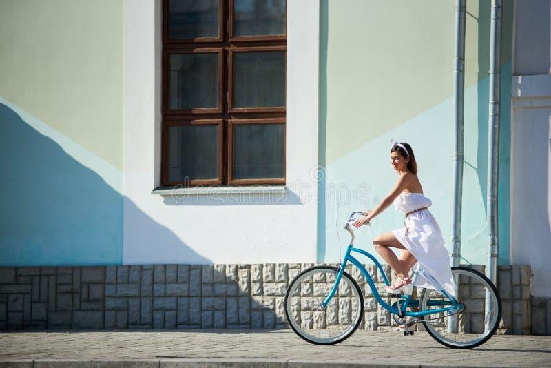 Dystyngowana kobieta jest jeździeckim błękitnym rocznika rowerem przy miasto ulicami zdjęcia royalty free