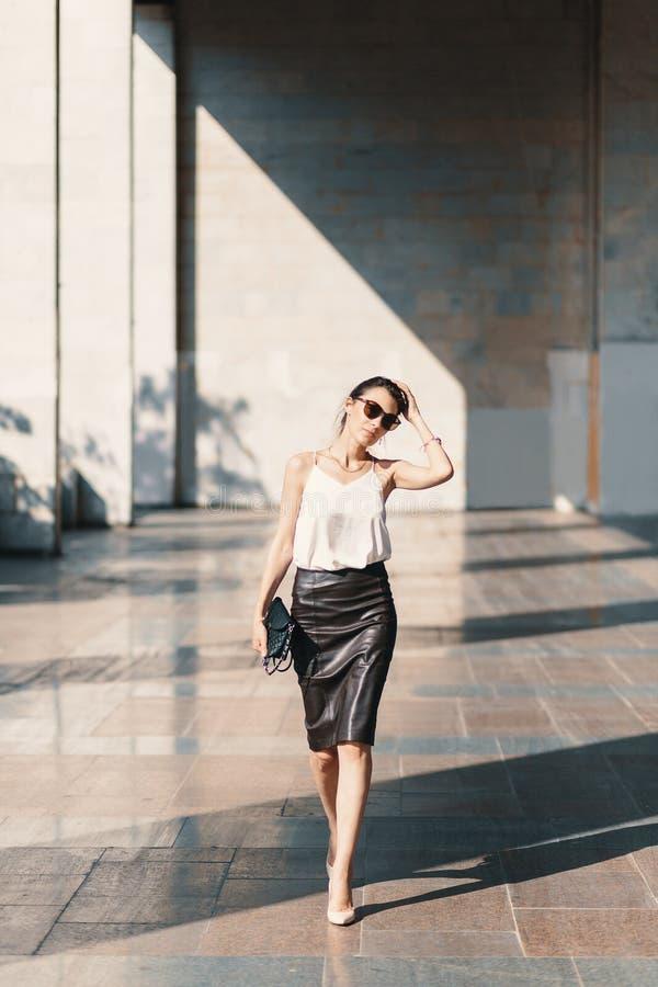 Dystyngowana młoda kobieta w skóra spódnicowym i jedwabniczym bluzki odprowadzenia przeciwie obrazy stock