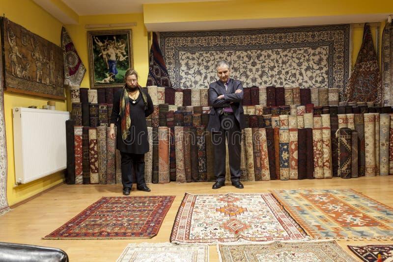 Dywanowy sprzedawca oferuje kolorowym orientalnym dywanom przy jego sklep zdjęcie royalty free