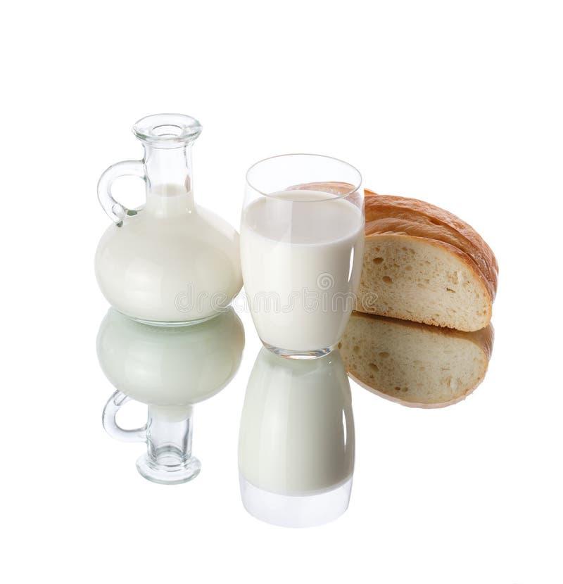 Dzbanek i szkło mleko z bochenkiem odizolowywającym na białym tle chleb zdjęcia stock