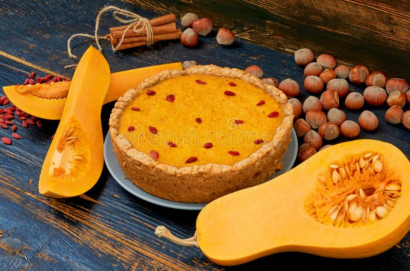 Dziękczynienie kulebiak z goji jagodą dekorującą z świeżymi bania plasterkami, cynamonowymi kijami i hazelnuts na drewnianym wieś obraz royalty free