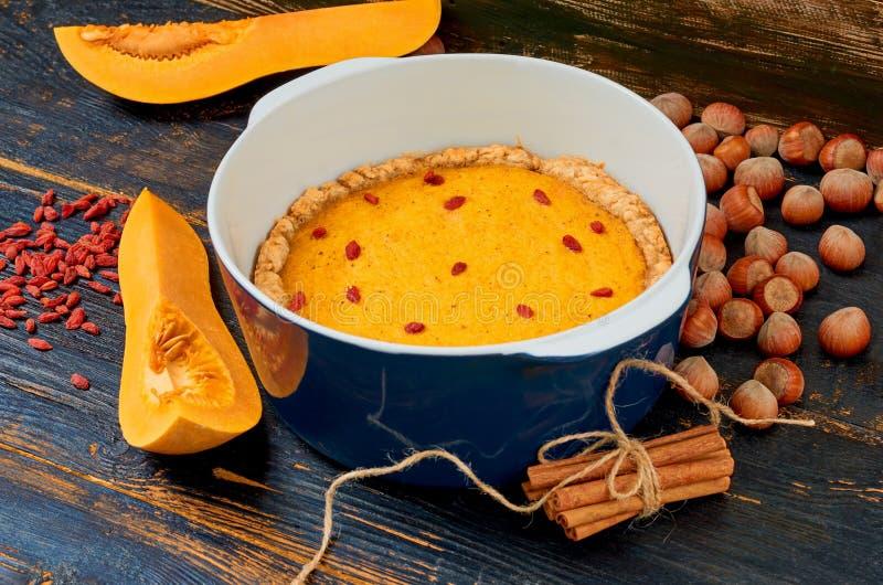 Dziękczynienie kulebiak z goji jagodą w wypiekowym naczyniu dekorującym z świeżymi dyniowymi plasterkami, cynamonowymi kijami i h zdjęcie royalty free
