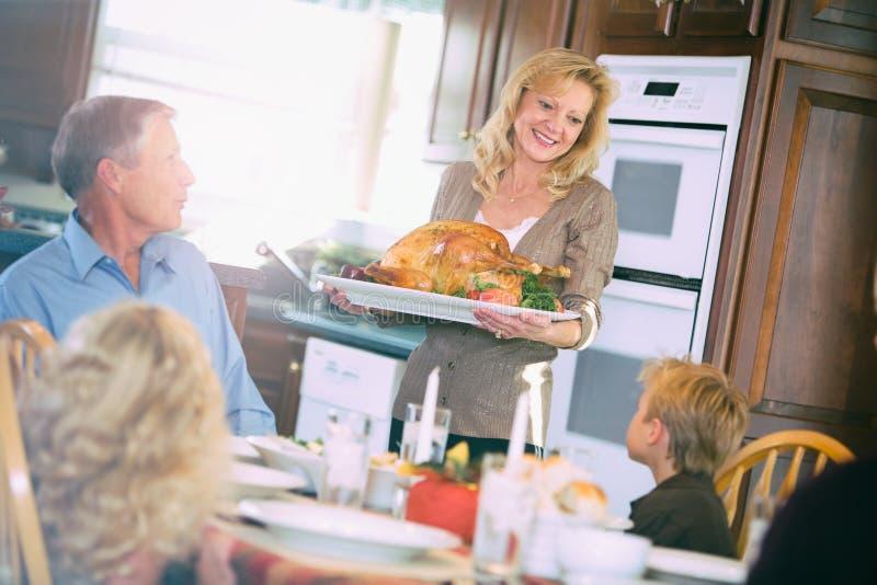 Dziękczynienie: Matka Przynosi Piec Turcja stół obraz stock