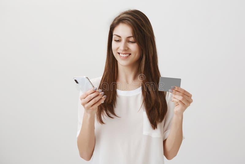 Dzięki jej bank kupował nowego telefon Portret zadowolony i skupiający się atrakcyjny kobiety mienia smartphone, ono uśmiecha się obrazy royalty free