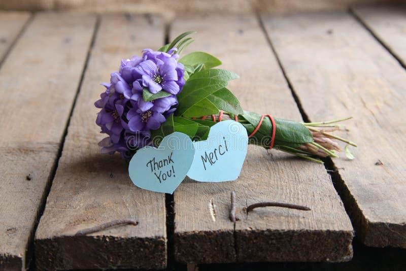 Dziękuje ciebie i Merci pisać na etykietce zdjęcie royalty free
