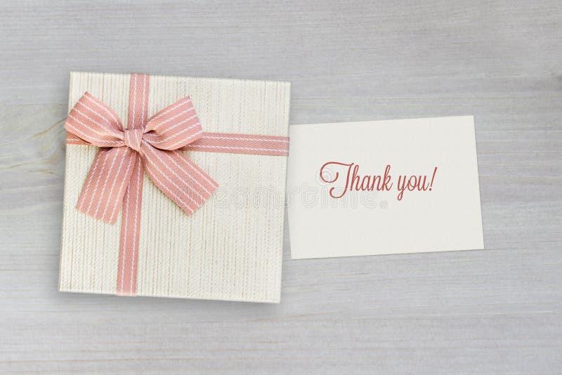 Dziękuje ciebie karcianego, prezenta pudełko z różowym faborkiem na drewnie fotografia royalty free