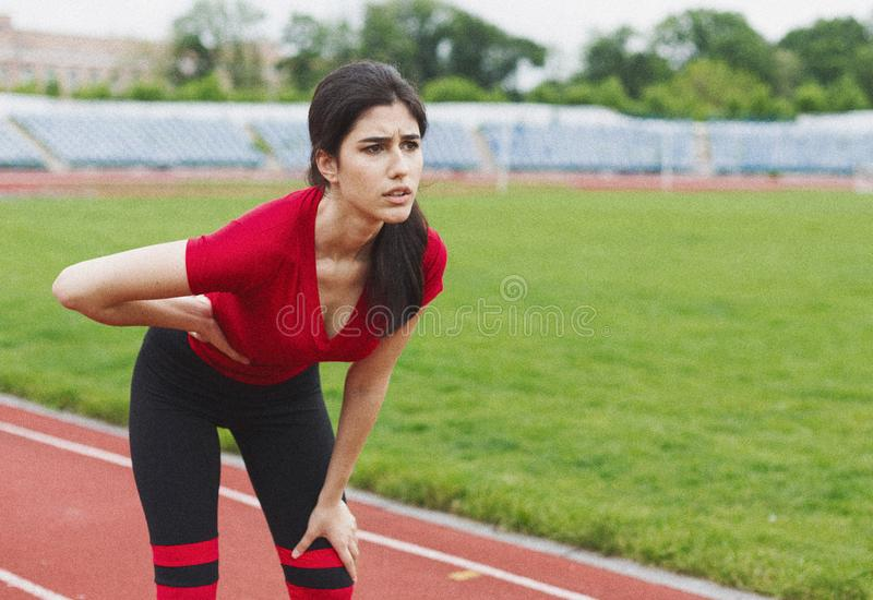 Działająca kobieta z żołądek strony bólem po jogging opracowywa zdjęcia stock