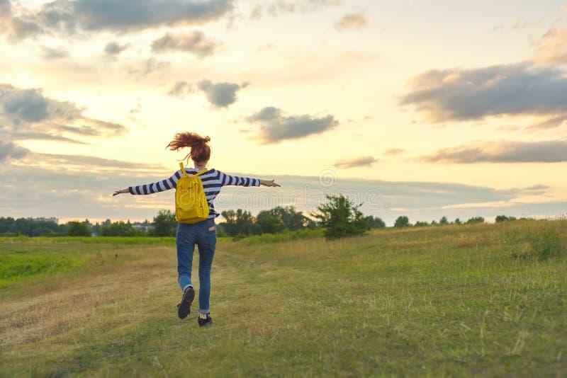 Działająca młoda dziewczyna z żółtym plecakiem, plecy z otwartymi rękami obrazy royalty free