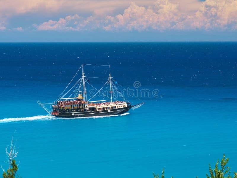 Działającego pirata corsair stylu łódkowaty statek w zadziwiać Grecja wyspy zatoki z dopłynięć ludźmi, plaża w Ionian morza błęki obraz royalty free