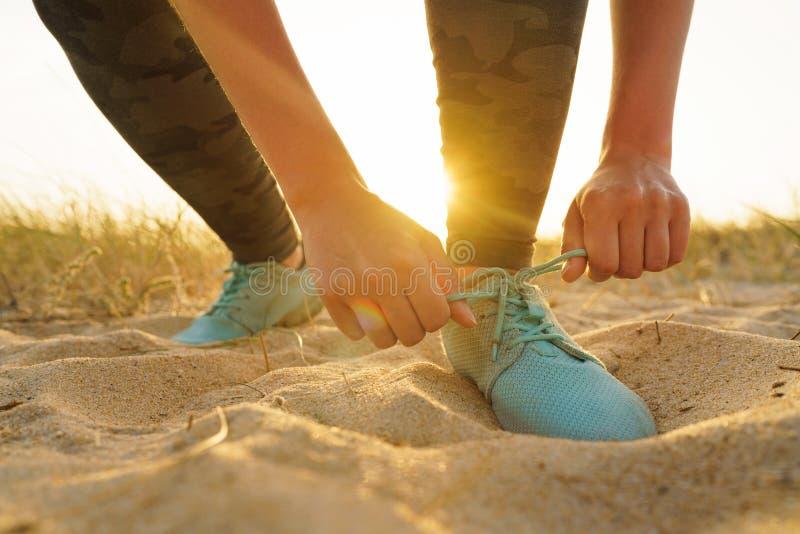 Działający buty - kobieta wiąże obuwiane koronki na piaskowatej plaży przy zmierzchem zdjęcia royalty free