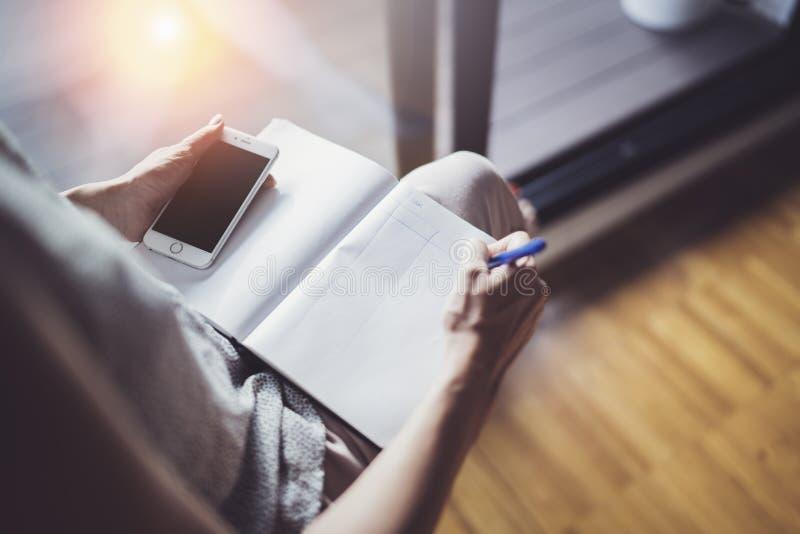działanie pojęcia w domu Przedsiębiorca biznesowa kobieta pisze notatkach i bierze używać jej papierową nutową książkę i telefon  zdjęcia royalty free