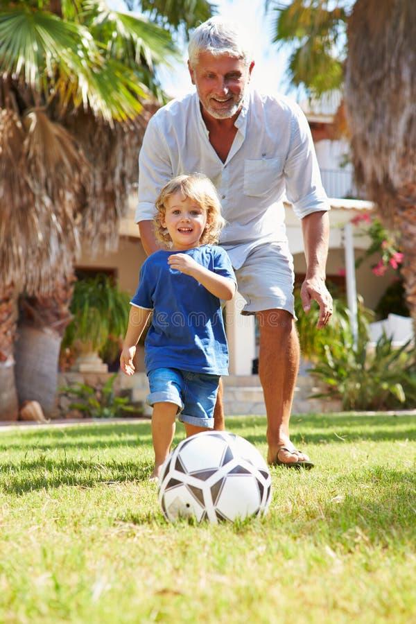 Dziad Bawić się futbol Z wnukiem W ogródzie obrazy royalty free