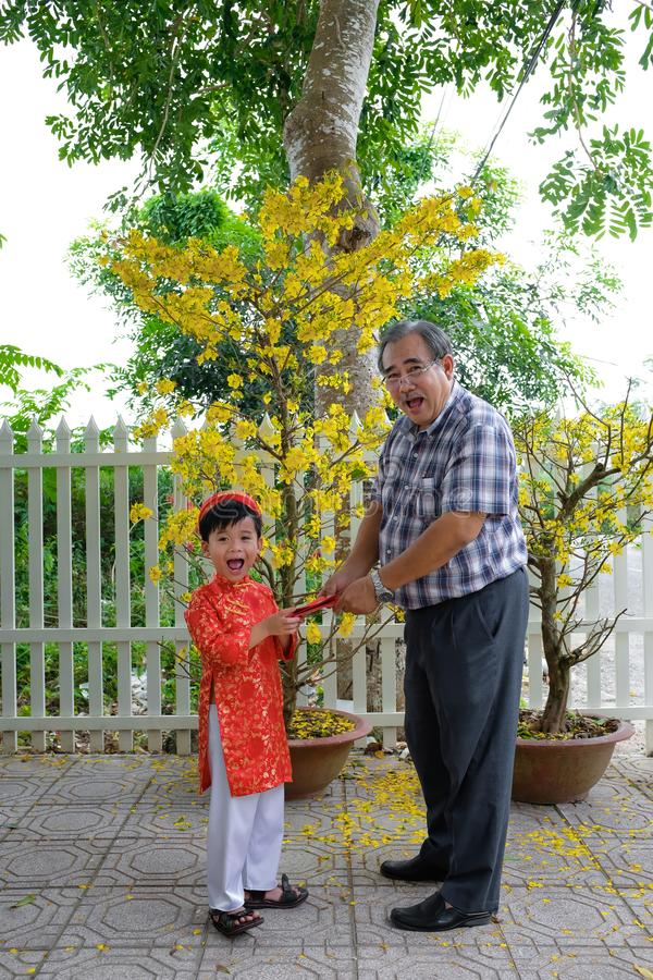Dziad daje szczęsliwemu pieniądze wnuk na pierwszy dniu Wietnamski księżycowy nowy rok Tet obraz stock