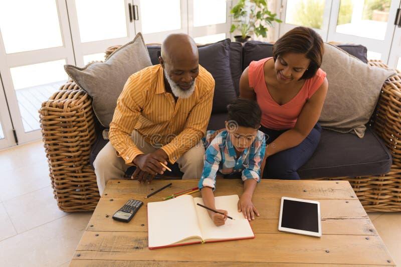 Dziad i babcia pomaga jego wnuka z pracą domową w żywym pokoju fotografia royalty free
