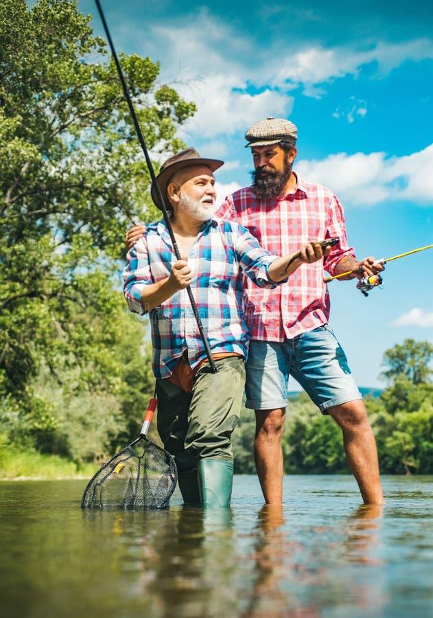 Dziad i chłopiec łowi wpólnie Szczęśliwy ojca i syna połów w rzecznych mienie połowu prąciach Brown pstr?g ryba zdjęcie royalty free
