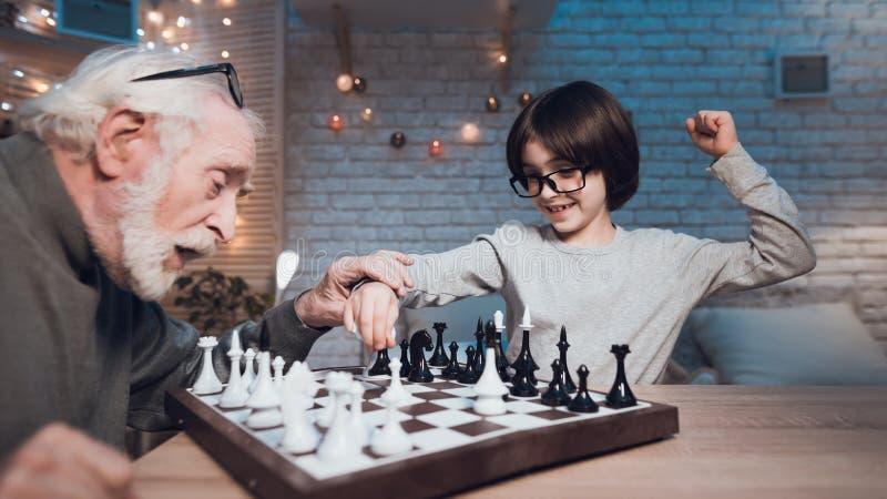 Dziad i wnuk bawić się szachy wpólnie przy nocą w domu Chłopiec wygrywa fotografia royalty free