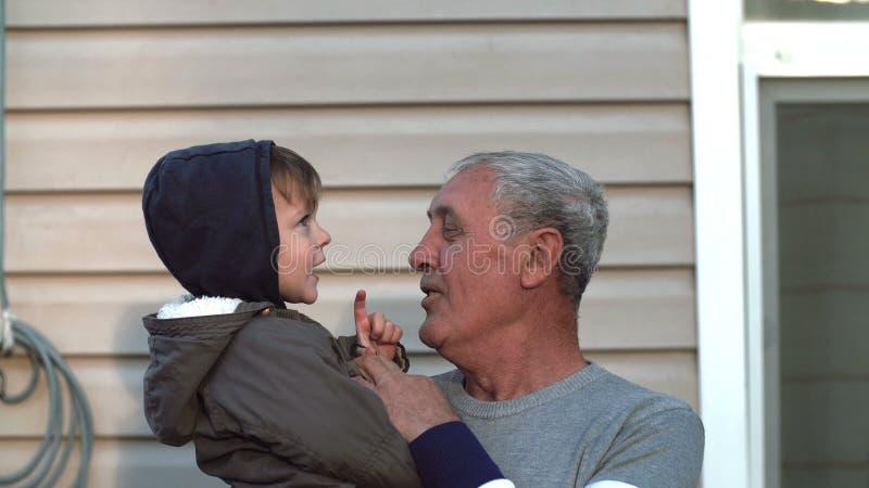 Dziad i wnuk opowiada, ono uśmiecha się, mieć zabawę, patrzeje kamera plenerowa Stary człowiek trzyma dalej ręki chłopiec 4K zdjęcia stock