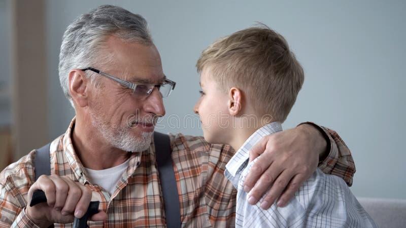 Dziad i wnuk patrzeje each inny w oczach, dwa pokolenia, zbliżenie obraz stock