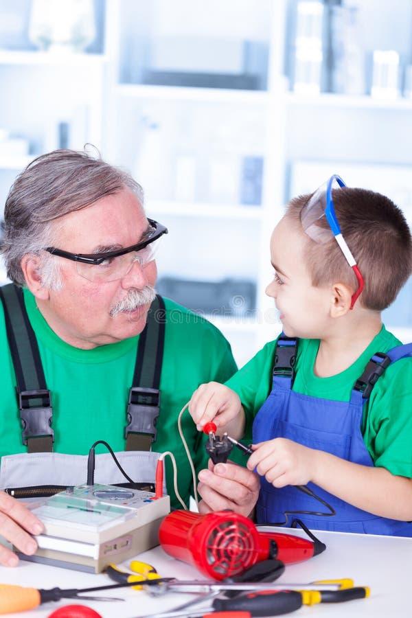 Dziad i wnuk używa multimeter zdjęcie royalty free