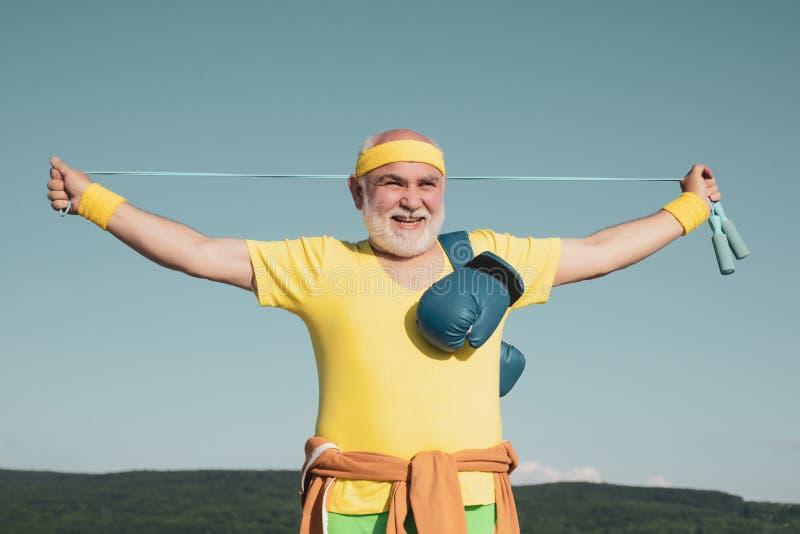 Dziad robi bokserskiemu szkoleniu w ranku Starszy sporta mężczyzna jest ubranym bokserskie rękawiczki Starszy chłodno mężczyzny b fotografia stock