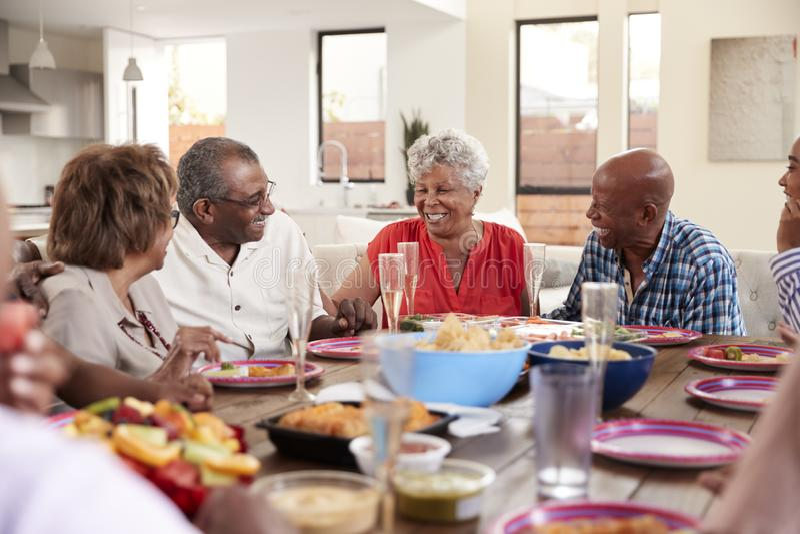 Dziad robi grzanki pozycji przy obiadowego sto?u od?wi?tno?ci? z jego rodzin?, zako?czenie w g?r? obrazy royalty free