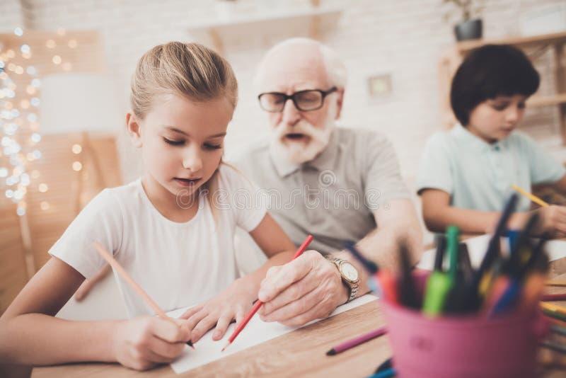 Dziad, wnuk i wnuczka, w domu Dzieci rysują obraz royalty free