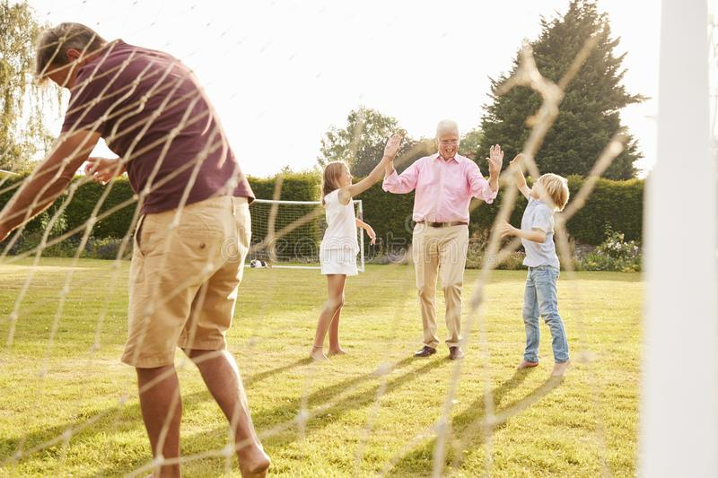 Dziadek, tata i nastoletni dzieciaki bawić się futbol, obraz stock