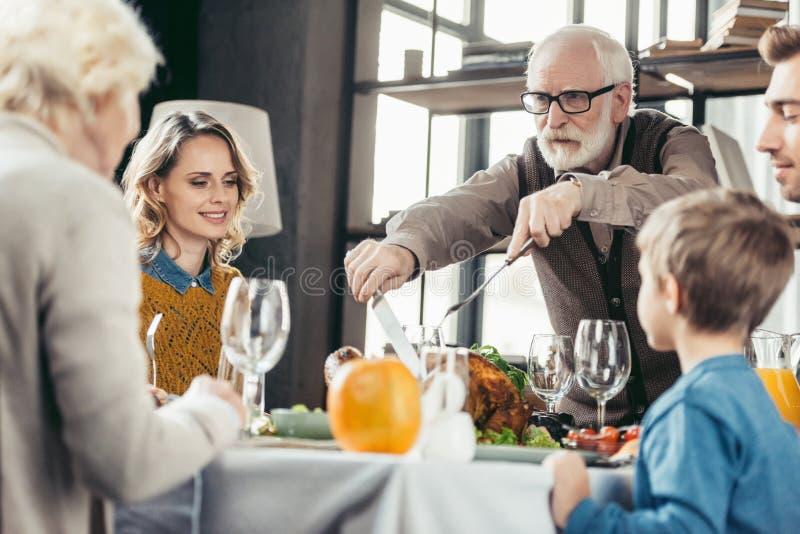 dziadek tnący indyk dla rodziny na dziękczynieniu fotografia stock