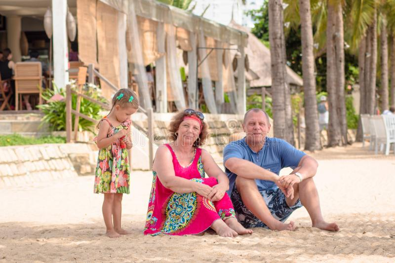 Dziadkowie cieszy się dzień z wnuczką blisko morza podczas gdy podmuchowi mydlani bąble na plaży fotografia stock