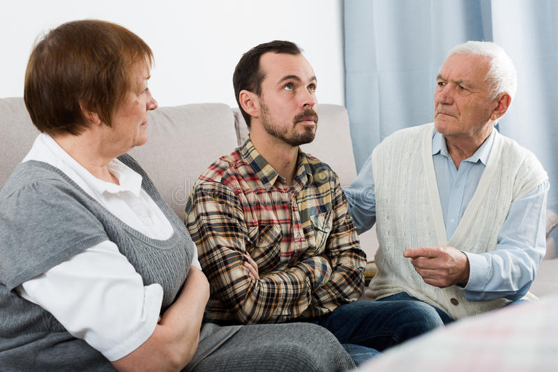 Dziadkowie i wnuk poważna rozmowa zdjęcie stock