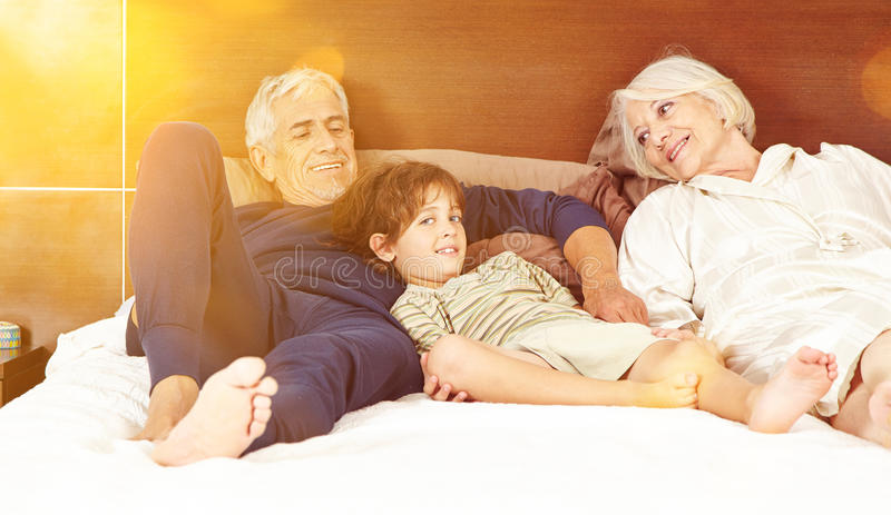 Dziadkowie z wnukiem na łóżku obraz royalty free