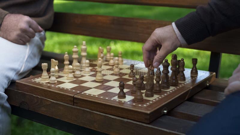 Dziady bawi? si? szachy na ?awce, rusza si? postacie na pok?adzie, gemowy pocz?tek zdjęcia stock