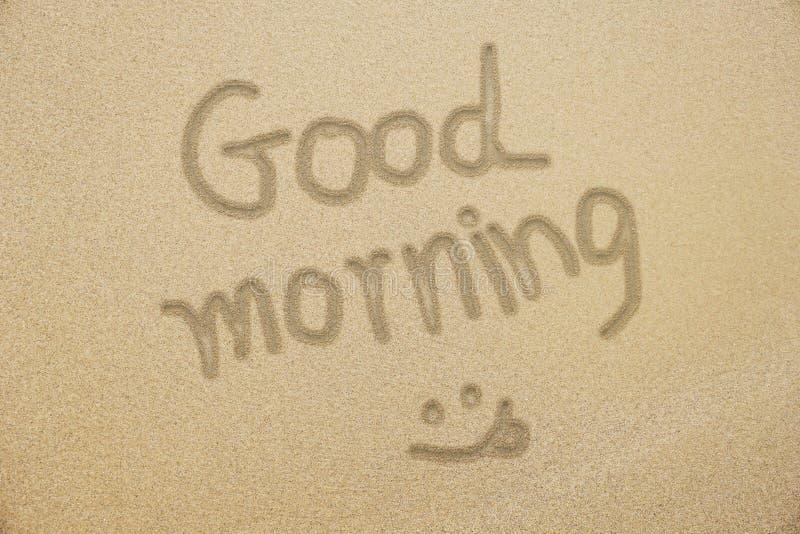 Dzień dobry ręki writing z uśmiechniętą twarzą na samd obraz stock
