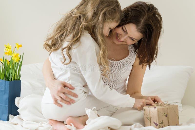 dzień kwiat daje mum syna matkom Matka ściska jej małej córki Tła wnętrze sypialnia, bukiet kwiaty, prezent, mama i dziecko, wewn fotografia stock