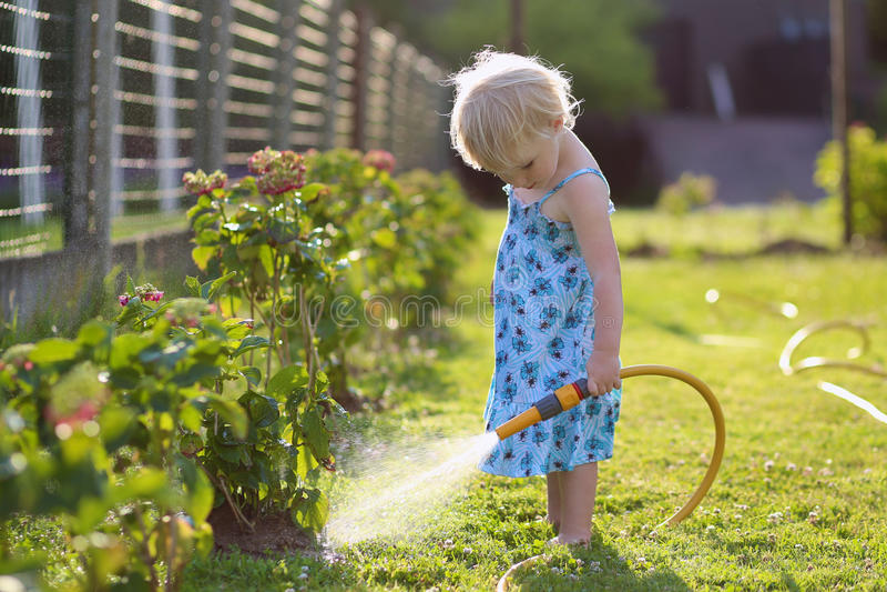dzień ogrodowej dziewczyny gorący mały rośliien lato podlewanie zdjęcia stock