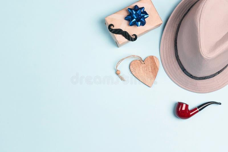 dzie? ojciec szcz??liwy s Kapelusz, prezenta pudełko, wąsy i tabaczna drymba na błękitnym tle, obraz stock