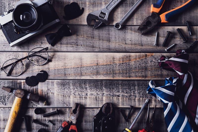 dzie? ojciec szcz??liwy s Odgórny widok granica narzędzia i krawaty, retro ekranowa kamera na ciemnym drewnianym stołowym tle Mie fotografia royalty free