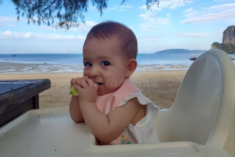 Dziecięca dziewczynka je ogórek na piaskowatej plaży zdjęcia stock