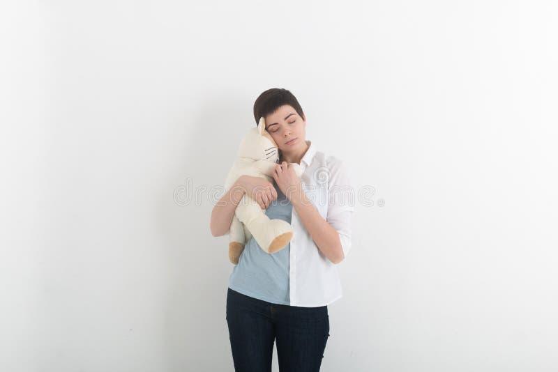 Dziecięca młodej kobiety przytulenia miękkiej części zabawka z niewinnie i smutnym romantycznym uśmiechem zdjęcia stock